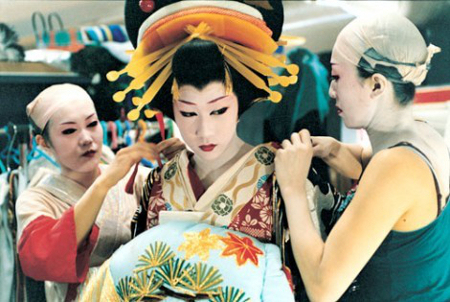 Onnegata performers assist a fellow actor with an extremely heavy wig and costume. The wig alone can weigh up to 30 lbs! Image via Azkabuki