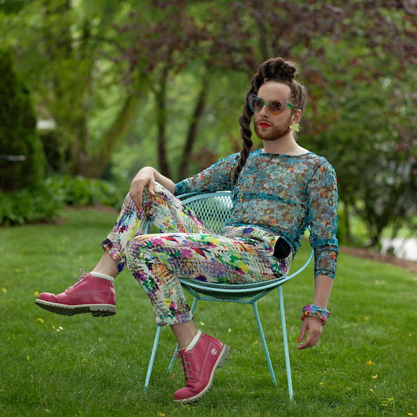 Picture of Harry sitting stretch across a metal chair in a field of grass, dressed in brighhtly colored patterned pants and aqua tight top, wearing pink converse sneakers.